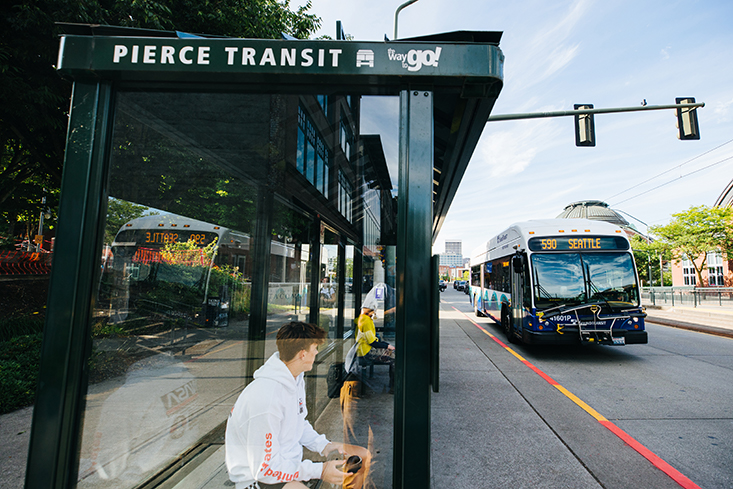 Rider waiting at a bus stop in downtown Tacoma. ST Express route 590 pulling up to stop.